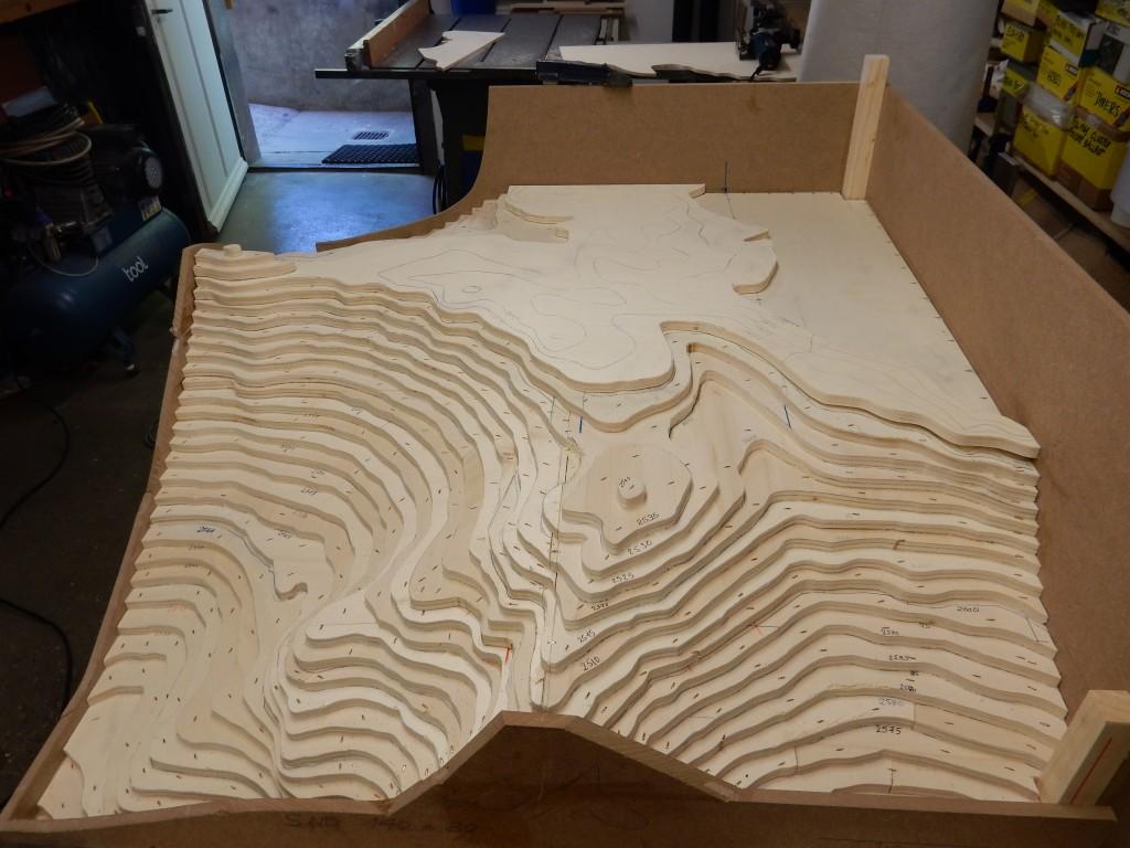 Fig 2: À partir du plan du site et de ses environs, le maquettiste découpe les courbes de niveau dans des planches de peuplier contreplaqué et les superpose pour donner le volume à la topographie de la maquette.