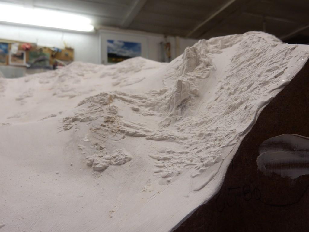 Fig. 4: Une fois les courbes montées, le relief est lissé. Les détails sont ensuite ajoutés avec un enduit blanc dans lequel seront modelées les falaises. Pour la moraine, le maquettiste concasse des plaques de céramiques et obtient de la poudre qu'il teint et colle sur la maquette.